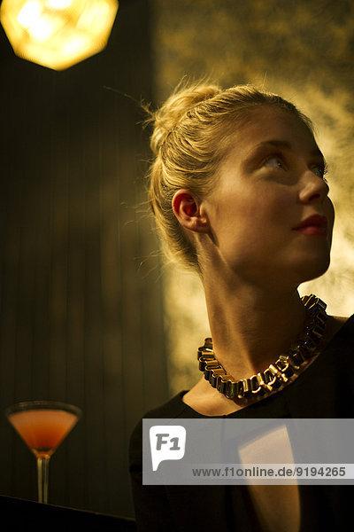 Frau sitzt allein in der Nachtclubbar und schaut erwartungsvoll weg.