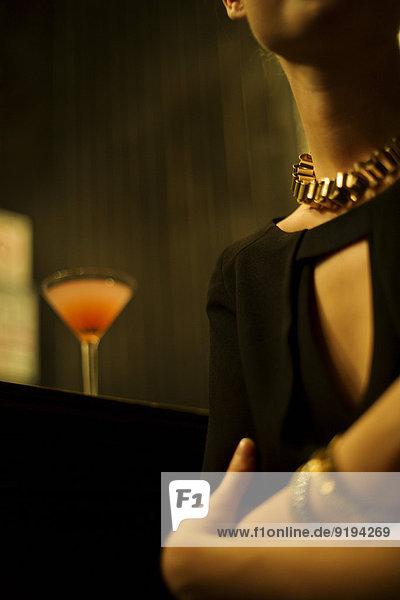 Frau sitzt allein in der Nachtclub-Bar