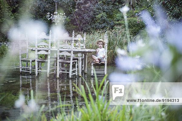 Kleiner Junge sitzt am Esstisch und schwimmt auf dem See.