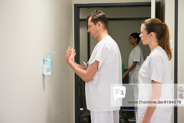 Male doctor using hygiene hand wash in hospital room