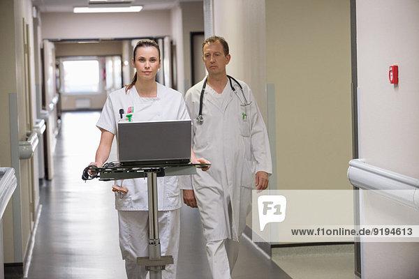 Ärztin und Krankenschwester mit Laptop in einem Krankenhausflur