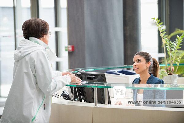Frau diskutiert an der Rezeption