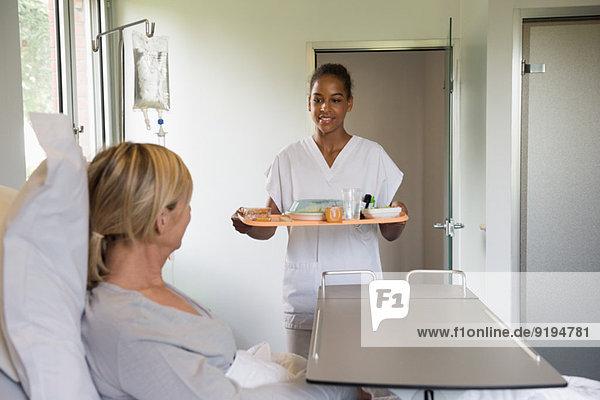 Krankenschwester  die dem Patienten Essen auf dem Krankenhausbett serviert.