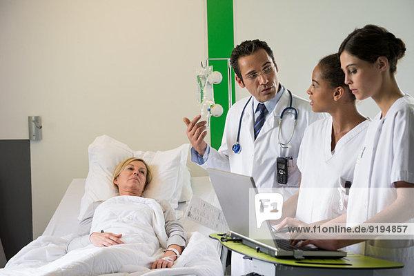 Medizinisches Team bespricht Patientinnenakte im Krankenhausbett