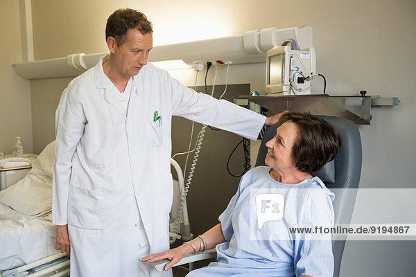 Male doctor assisting female patient in hospital