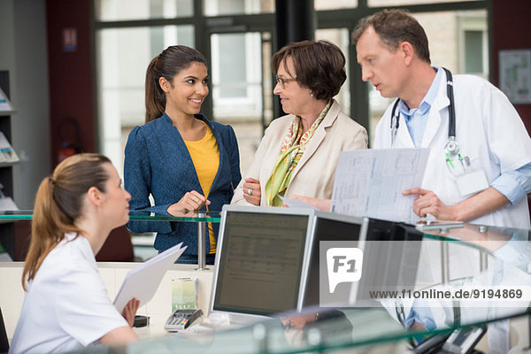 Male doctor discussing with receptionist at hospital reception desk