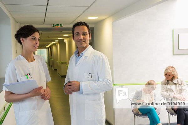 Doctor and nurse standing in hospital corridor with patients sitting in waiting area