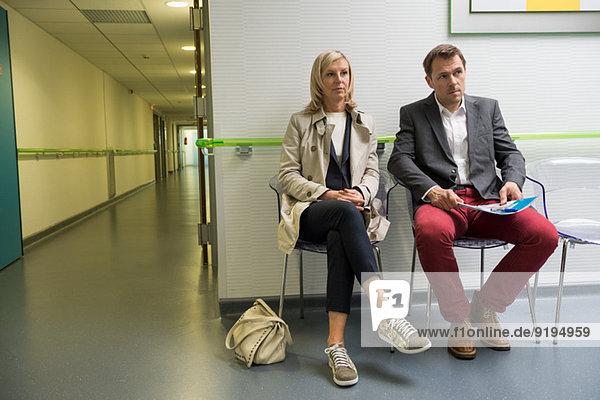 Paar im Wartebereich eines Krankenhauses sitzend