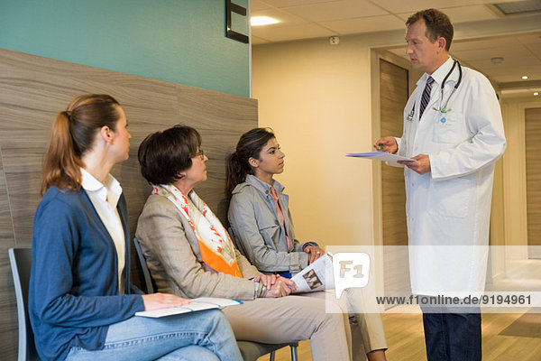 Male doctor discussing with his patients in waiting room