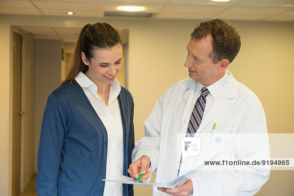 Male doctor discussing medical report with a woman in hospital