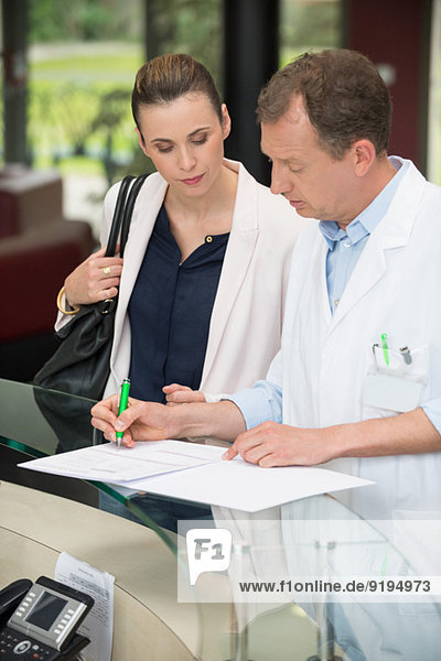Two doctors discussing report at hospital reception desk