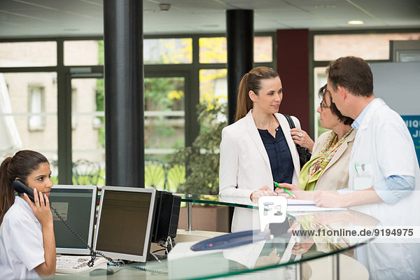 Doctors discussing with patient at hospital reception desk