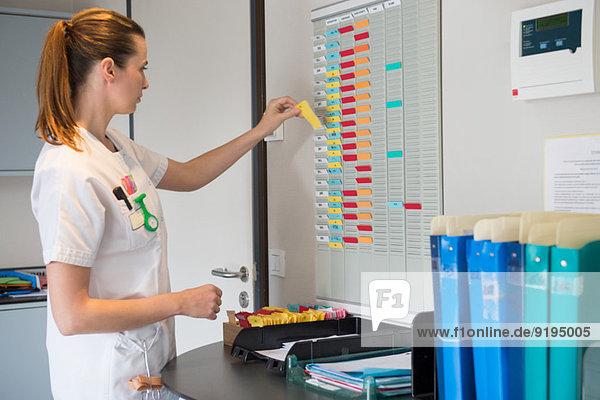 Krankenschwester arrangiert Zeitplan im Krankenhaus