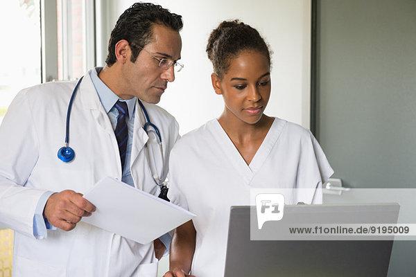 Arzt und Krankenschwester besprechen Aufzeichnung auf einem Laptop im Krankenhaus