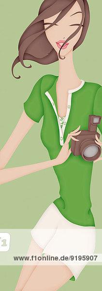 Glückliche schöne Frau in Shorts hält eine Kamera