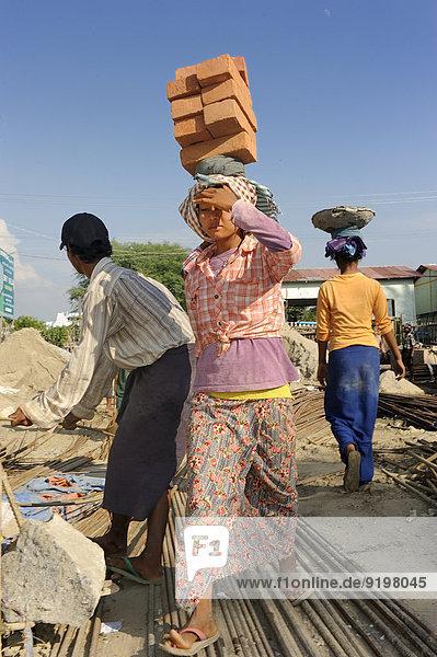 Bauarbeiterinnen tragen Backsteine auf dem Kopf  auf einer Hochhausbaustelle  Mandalay  Myanmar
