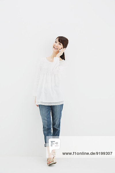 Japanese young woman in jeans and white shirt with smartphone standing against white background
