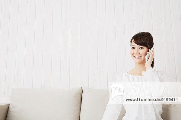 junge Frau junge Frauen Couch weiß Hemd japanisch Smartphone