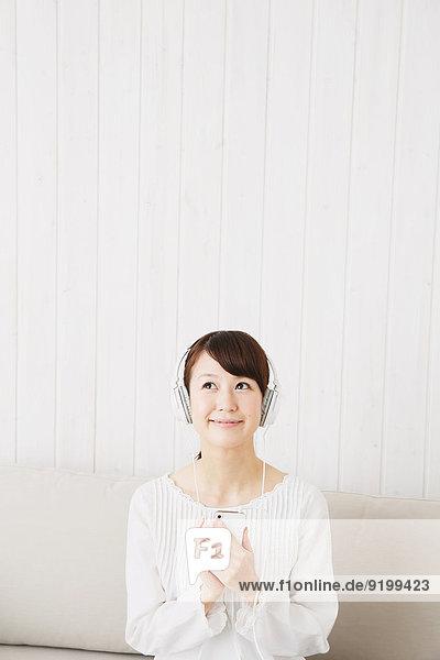 junge Frau junge Frauen Couch weiß Hemd Kopfhörer japanisch
