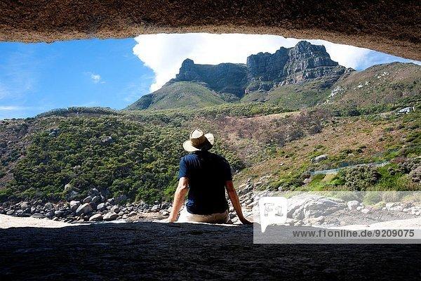 Südliches Afrika Südafrika zwischen inmitten mitten Felsbrocken Berg Mann sitzend Hut hinaussehen Kleidung Atlantischer Ozean Atlantik Bucht Kapstadt Granit