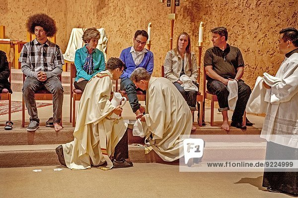 The robed pastor of St. Timothy's Catholic Church  Laguna Niguel  CA  washes the feet of parishioners on Holy Thursday mass in memory of Christ washing the feet of his disciples at the Last Supper. Note age range.