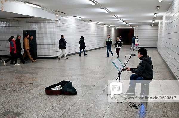 Chinese teen playing guitar and singing for money in underground passage in Beijing  China.