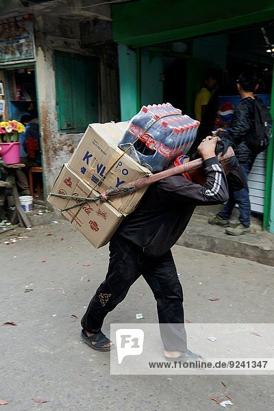 A man carries heavy boxes and Coca Cola in the Chowrasta street market.