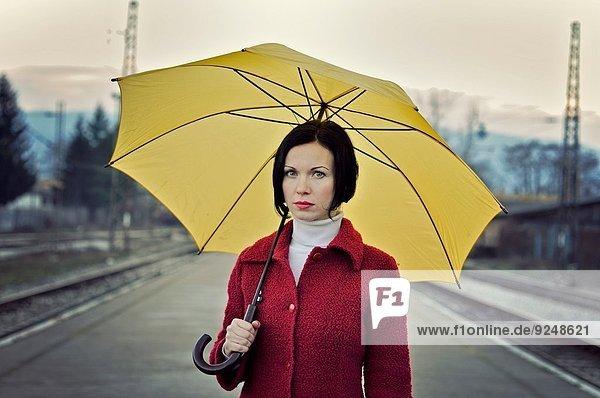 Frau Regenschirm Schirm gelb halten