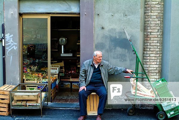 Elderly man sitting on a box outside a greengrocery shop (Perugia  Umbria).