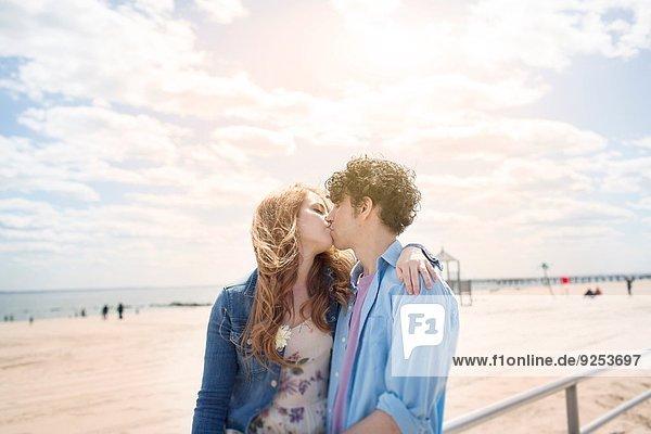 Romantisches Paar beim Küssen am Strand
