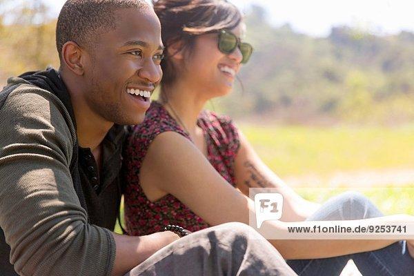 Romantisches junges Paar in ländlicher Sonne sitzend
