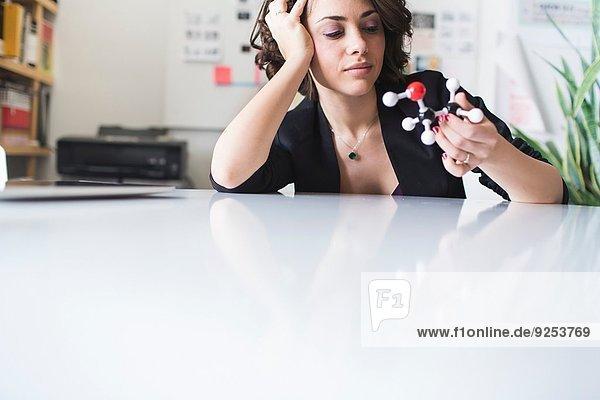 Junge Frau betrachtet molekulares Modell des Ethanolmoleküls Junge Frau betrachtet molekulares Modell des Ethanolmoleküls