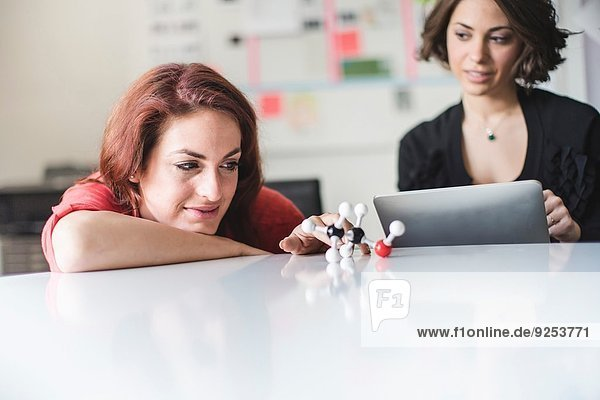 Junge Frauen diskutieren über das molekulare Modell eines Ethanolmoleküls