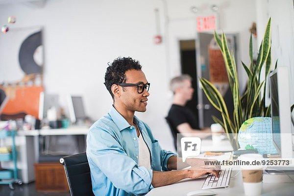 Junger Mann arbeitet am Computer im Büro