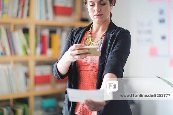 Junge Frau hinterlegt Scheck mit Smartphone