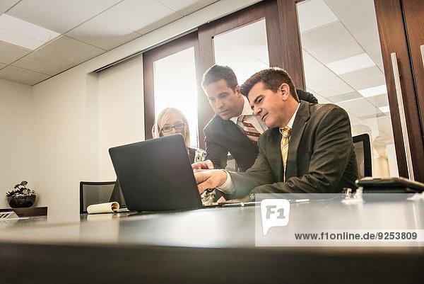 Drei Wirtschaftsanwälte bei einem Planungsgespräch im Büro
