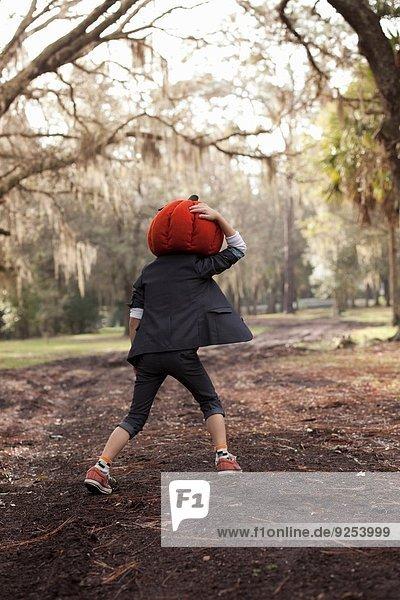 Junge rennt im Wald und hält sich am Kürbiskopf fest.