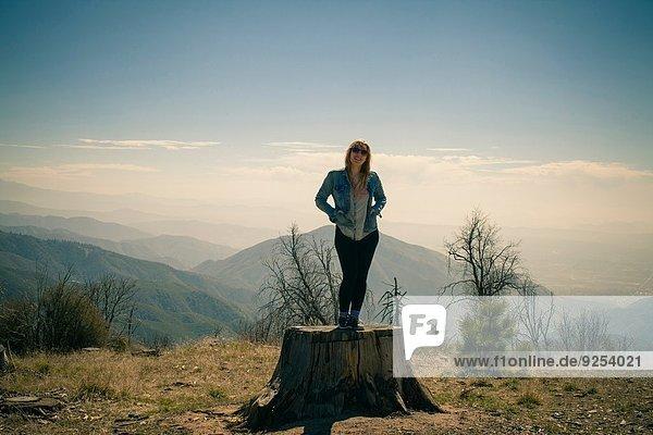 Porträt einer erwachsenen Frau auf einem Baumstamm  Lake Arrowhead  Kalifornien  USA
