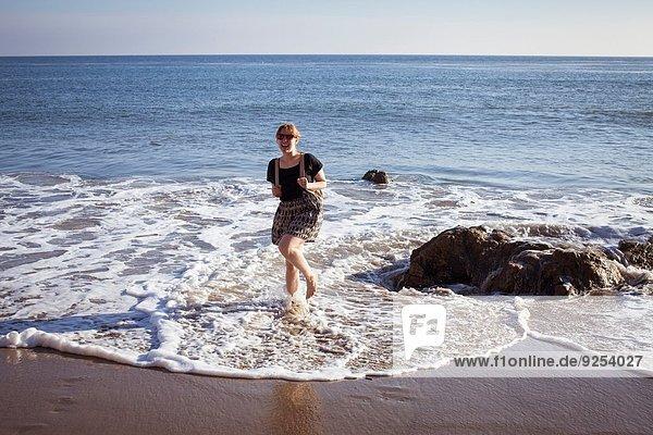 Porträt einer mittleren erwachsenen Frau beim Paddeln im Meer  Malibu  Kalifornien  USA