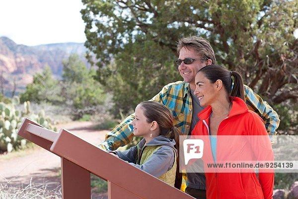 Mature parents and daughter reading sign whilst hiking  Sedona  Arizona  USA