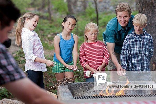 Mature couple and four children toasting marshmallows on campsite  Sedona  Arizona  USA