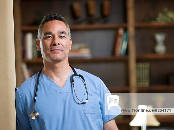 Portrait of smiling mature doctor in office