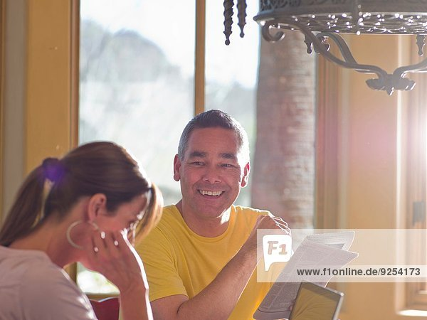 Mature couple with laptop and newspaper in dining room