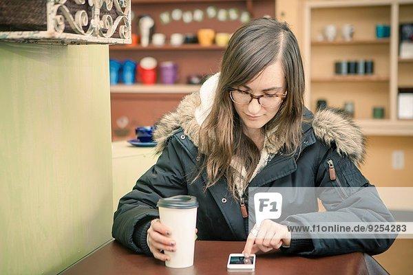 Mid Erwachsene Frau SMS auf dem Smartphone im Cafe