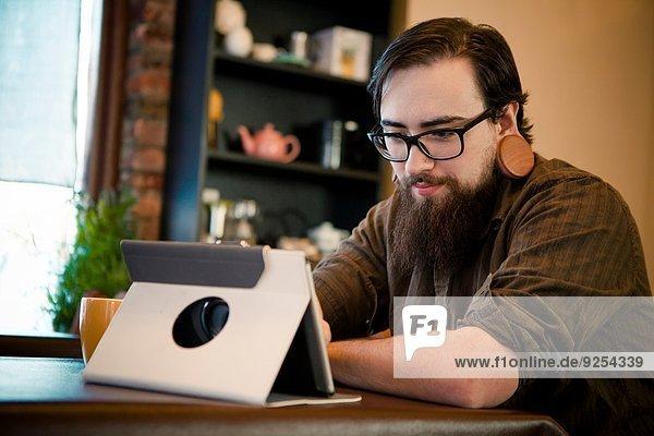 Junger Mann trinkt Kaffee und benutzt digitale Tabletten im Cafe