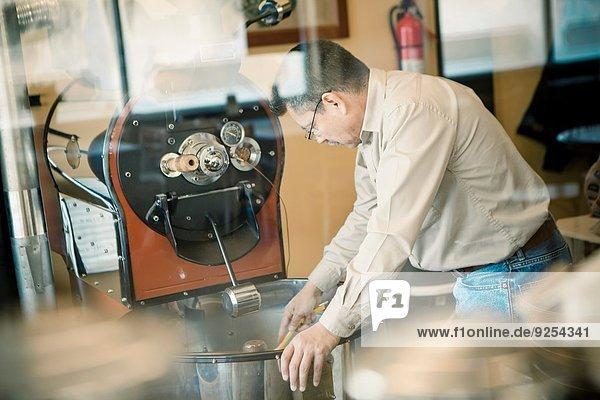 Reifer Mann mit Kaffeerösterei im Cafe