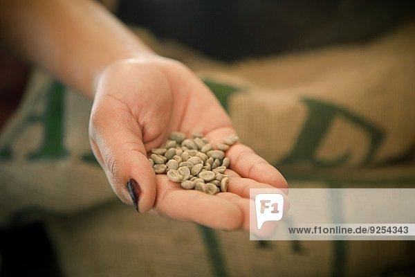 Nahaufnahme der Frauenhand mit rohen Kaffeebohnen im Cafe