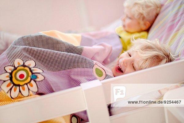 Zwei junge Brüder liegen im Bett  einer lacht.