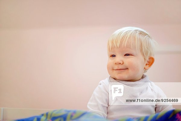 Porträt eines süßen vierzehn Monate alten Jungen  der auf einer Bettdecke sitzt.