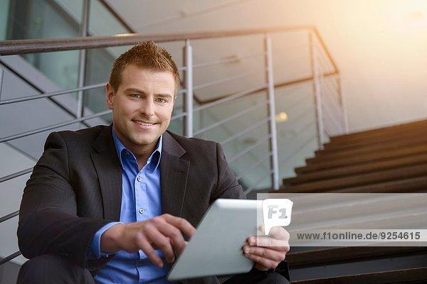 Portrait eines Geschäftsmannes mit digitalem Tablett auf der Bürotreppe